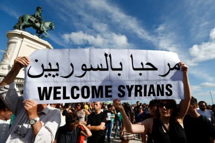 epa04927475 People take part in a demonstration in support of migrants holding up placards saying 'Syrians Refugees welcome', in Lisbon, Portugal, 12 September 2015.  EPA/ANTONIO COTRIM